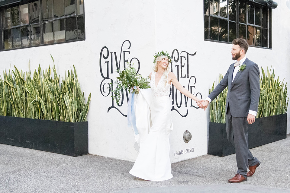 luce-loft-bride-and-groom-walking-outside-bride-in-a-fit-and-flare-gown-with-straps-groom-in-a-charcoal-suit-with-champagne-bow-tie