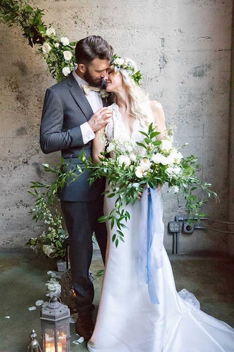 luce-loft-couple-at-ceremony-space-bride-in-a-fit-and-flare-gown-with-straps-groom-in-a-charcoal-suit-with-champagne-bow-tie