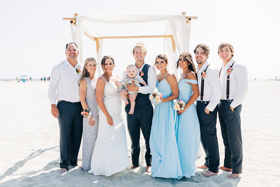 San-Diego-Beach-wedding-bridal-party-smiling-bridesmaids-in-bright-blue-dresses-groomsmen-in-suit-pants-and-suspenders-bride-ina-lace-formitting-dress-with-strapsand-a-veil-groom-in-a-suit-pants-and-vest