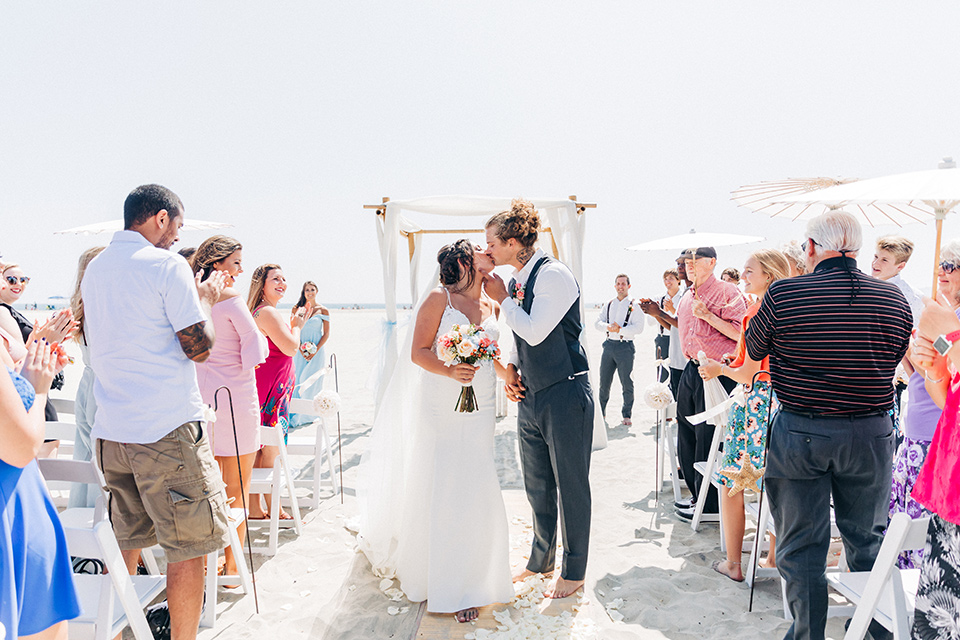 San-Diego-Beach-wedding-bride-and-groom-kissing-at-end-of-aisle-bridesmaids-in-bright-blue-dresses-groomsmen-in-suit-pants-and-suspenders-bride-ina-lace-formitting-dress-with-strapsand-a-veil-groom-in-a-suit-pants-and-vest