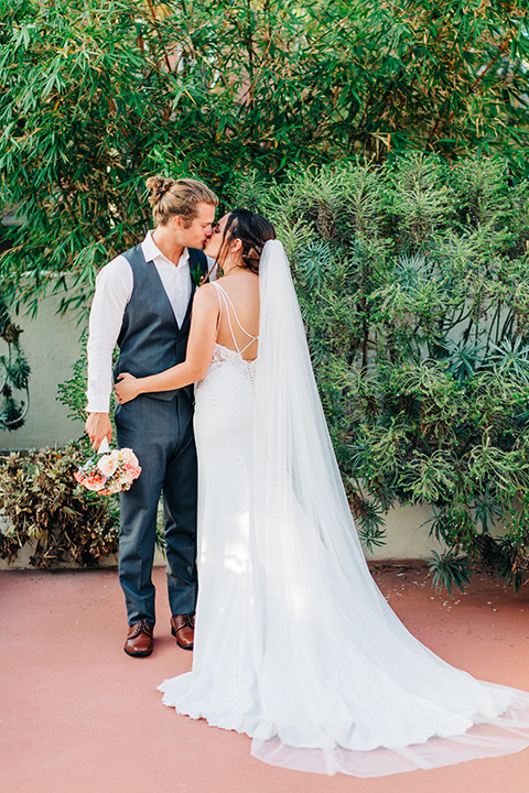 San-Diego-Beach-wedding-bride-and-groom-kissing-bride-in-a-lace-form-fitting-dress-with-straps-groom-in-a-casual-look-with-vest-and-pants-in-a-grey-suit-color