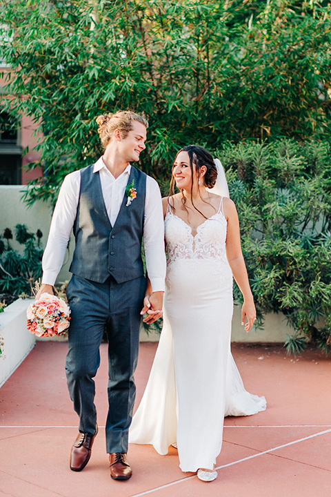 San-Diego-Beach-wedding-bride-and-groom-walking-groom-in-a-grey-suit-pant-and-vest-bride-in-a-casual-lace-gown