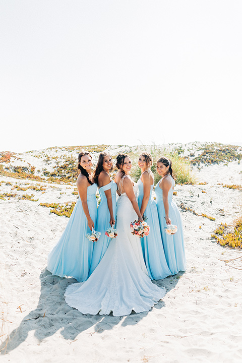 San-Diego-Beach-wedding-bridesmaids-back-to-camera-in-blue-flowing-gowns-and-the-bride-in-a-lace-fitted-gown