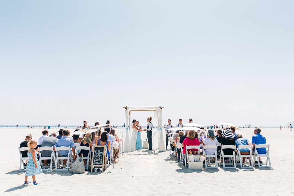 San-Diego-Beach-wedding-ceremony-bridesmaids-in-bright-blue-dresses-groomsmen-in-suit-pants-and-suspenders-bride-ina-lace-formitting-dress-with-strapsand-a-veil-groom-in-a-suit-pants-and-vest