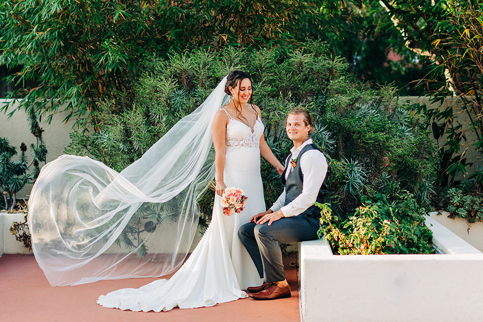 San-Diego-Beach-wedding-groom-sitting-brode-stands-with-veil-in-the-wind-bride-ina-lace-formitting-dress-with-straps-and-a-veil-groom-in-a-suit-pants-and-vest