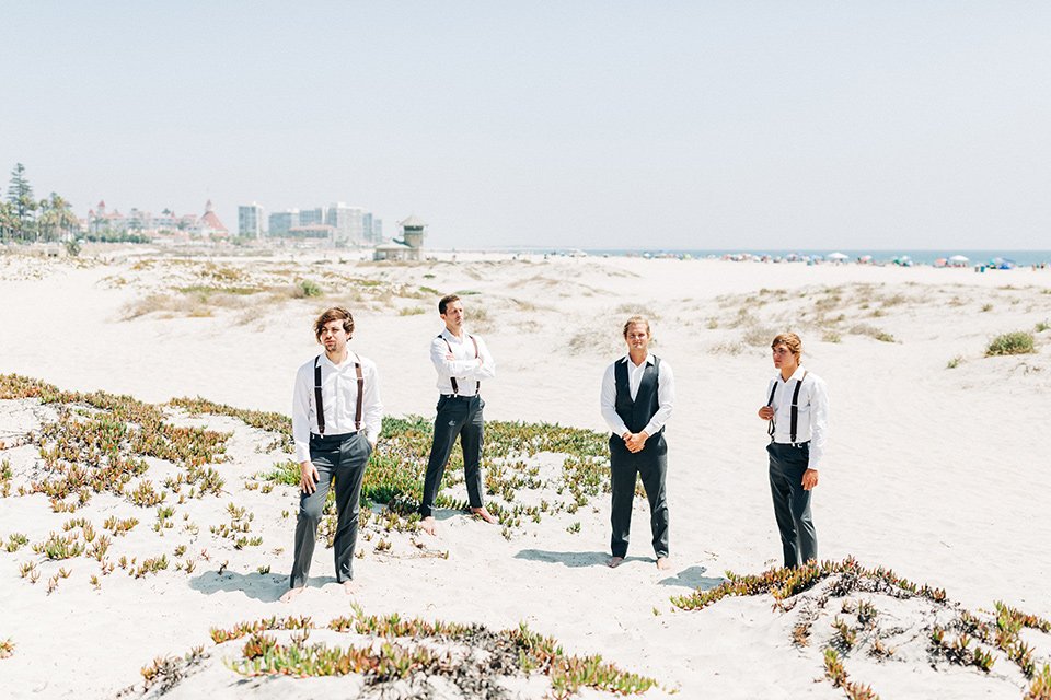 San-Diego-Beach-wedding-groomsmen-groomsmen-in-suit-pants-and-suspenders-bride-ina-lace-formitting-dress-with-strapsand-a-veil-groom-in-a-suit-pants-and-vest