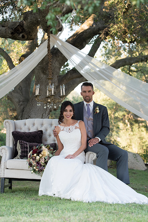 milagro-farms-shoot-bride-and-groom-in-outside-space-bride-in-a-fitted-lace-gown-with-straps-groom-in-a-charcoal-suit-with-a-purple-tie