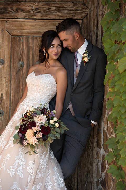 milagro-farms-shoot-bride-and-groom-leaning-against-each-other-by-door-bride-in-a-fitted-lace-gown-with-straps-groom-in-a-charcoal-suit-with-a-purple-tie
