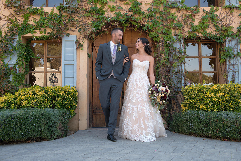 milagro-farms-shoot-bride-and-groom-walking-bride-in-a-fitted-lace-dress-groom-in-charcoal-suit-with-purple-tie