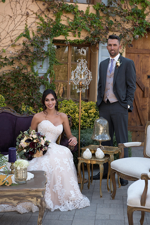 milagro-farms-shoot-bride-sitting-groom-standing-bride-in-a-fitted-lace-gown-with-straps-groom-in-a-charcoal-suit-with-a-purple-tie