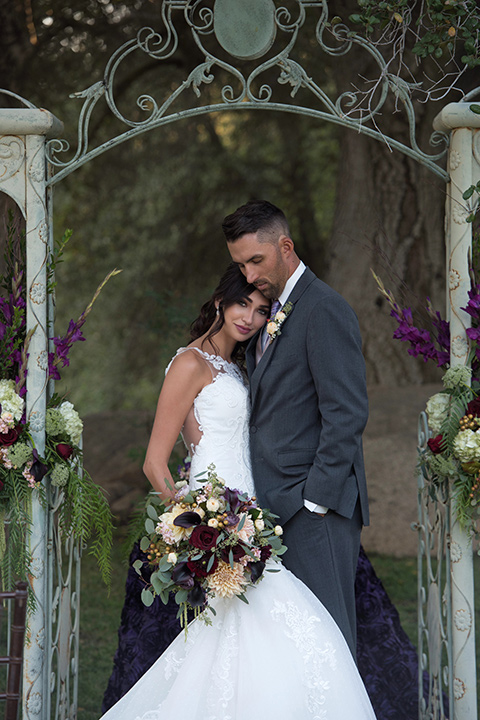 milagro-farms-shoot-couple-at-ceremony-sace-bride-in-a-fitted-lace-gown-with-straps-groom-in-a-charcoal-suit-with-a-purple-tie