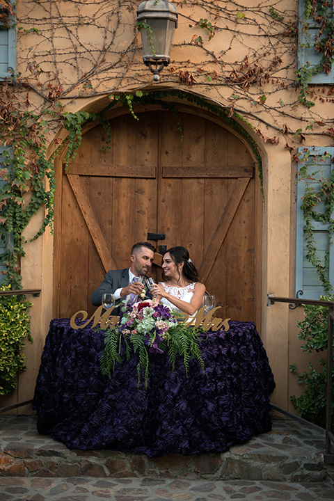 milagro-farms-shoot-sweetheart-table-bride-in-a-fitted-lace-gown-with-straps-groom-in-a-charcoal-suit-with-a-purple-tie