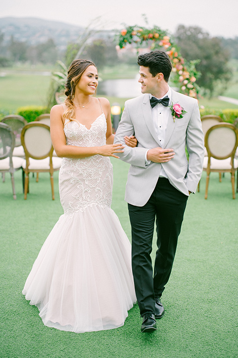 omni-la-costa-bride-and-groom-walking-down-ceremony-bride-wearing-a-lace-fitted-gown-with-mermaid-style-with-thin-straps-groom-with-light-grey-jacket-with-black-pants-black-polka-dot-bowtie