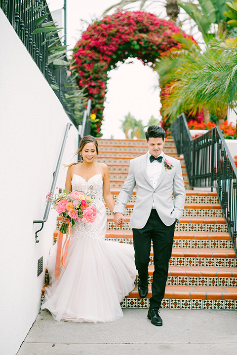 omni-la-costa-bride-and-groom-walking-down-the-stairs-bride-wearing-a-lace-fitted-gown-with-mermaid-style-with-thin-straps-groom-with-light-grey-jacket-with-black-pants-black-polka-dot-bowtie