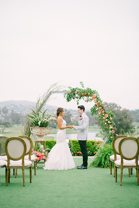 omni-la-costa-ceremony-space-bride-wearing-a-lace-fitted-gown-with-mermaid-style-with-thin-straps-groom-with-light-grey-jacket-with-black-pants-black-polka-dot-bowtie