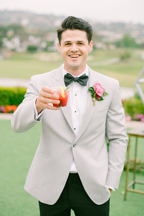 omni-la-costa-groom-with-drink-bride-wearing-a-lace-fitted-gown-with-mermaid-style-with-thin-straps-groom-with-light-grey-jacket-with-black-pants-black-polka-dot-bowtie