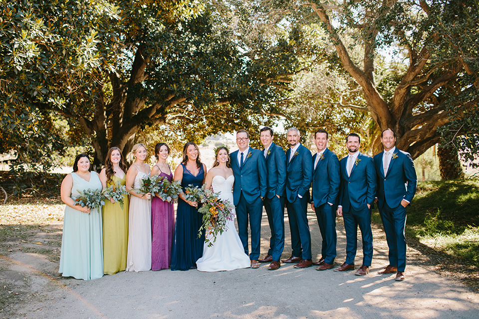 Dos-pueblos-orchid-farm-wedding-bridalparty-standing-in-a-line-where-the-brides-are-in-multicolored-gowns-and-groomsmen-in-dark-blue-suits-the-bride-wore-a-fitted-lace-mermaid-gown-and-groom-wore-a-dark-blue-suit
