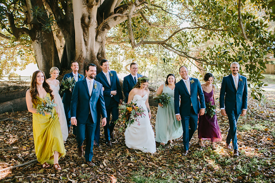 Dos-pueblos-orchid-farm-wedding-bridalparty-walking-away-bridesmaids-wore-different-colored-gowns-groomsmen-wore-navy-suits-bride-in-fitted-mermaid-gown-groom-in-navy-suit