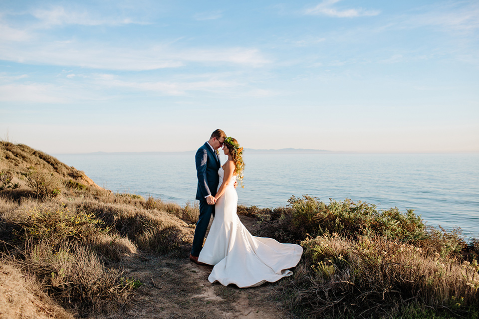 Dos-pueblos-orchid-farm-wedding-bride-and-groom-by-ocean-groom-in-a-fitted-navy-suit-bride-in-a-bohemian-mermaid-gown