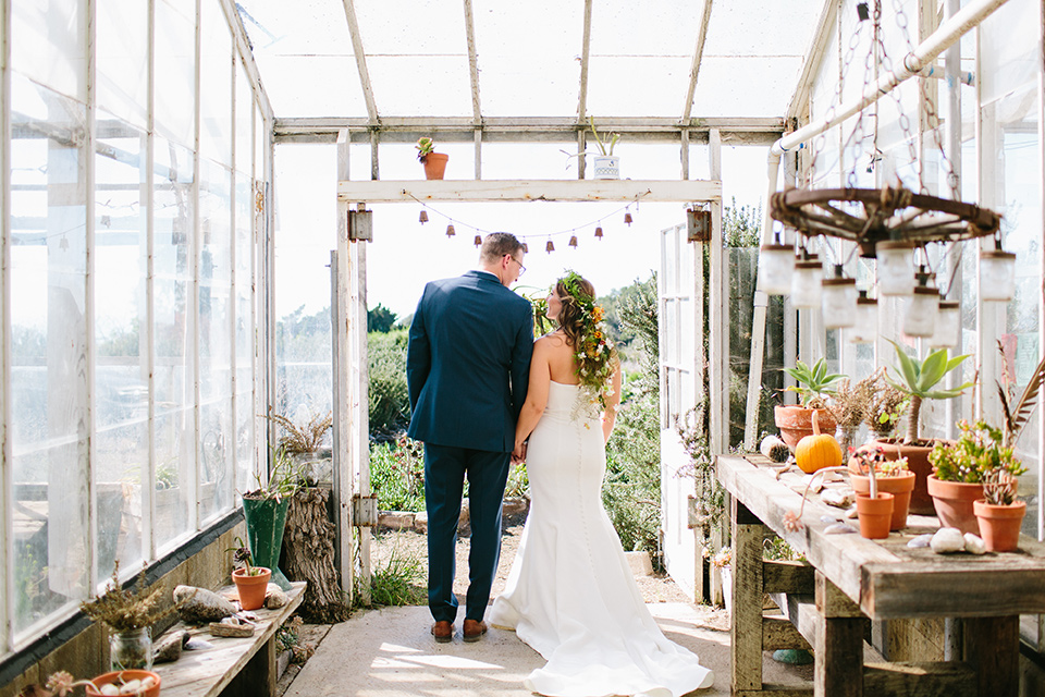 Dos-pueblos-orchid-farm-wedding-bride-and-groom-looking-out-windows-groom-in-a-fitted-navy-suit-bride-in-a-bohemian-mermaid-gown