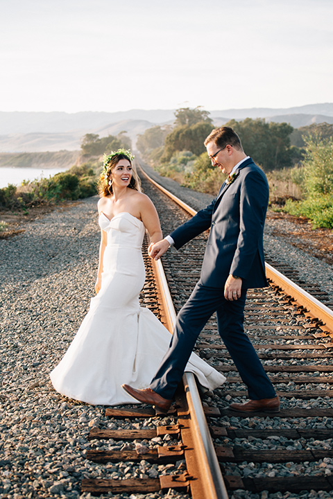 Dos-pueblos-orchid-farm-wedding-bride-and-groom-walking-across-the-train-tracks-bride-in-a-fitted-gown-groom-in