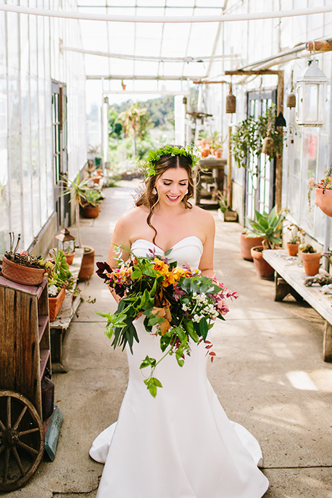 Dos-pueblos-orchid-farm-wedding-bride-standing-alone-in-glass-building-in-a-fitted-gown-and-a-floral-crown