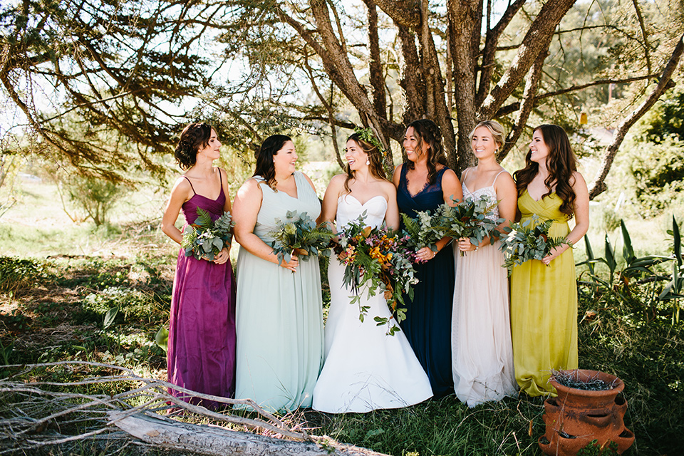 Dos-pueblos-orchid-farm-wedding-bridesmaids-and-bride-standing-under-a-tree-the-bridesmaids-in-multicolored-gowns-and-thebride-in-a-strapless-boho-inspired-gown