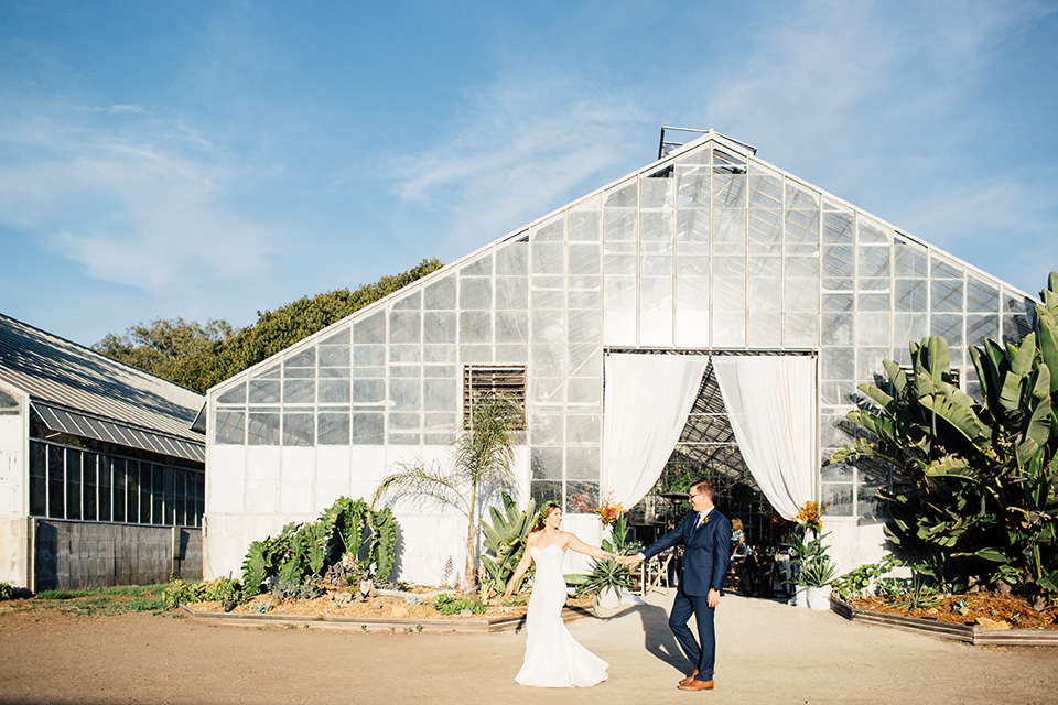 Dos-pueblos-orchid-farm-wedding-brode-and-groom-walking-across-glass-building-groom-in-a-fitted-navy-suit-bride-in-a-bohemian-mermaid-gown