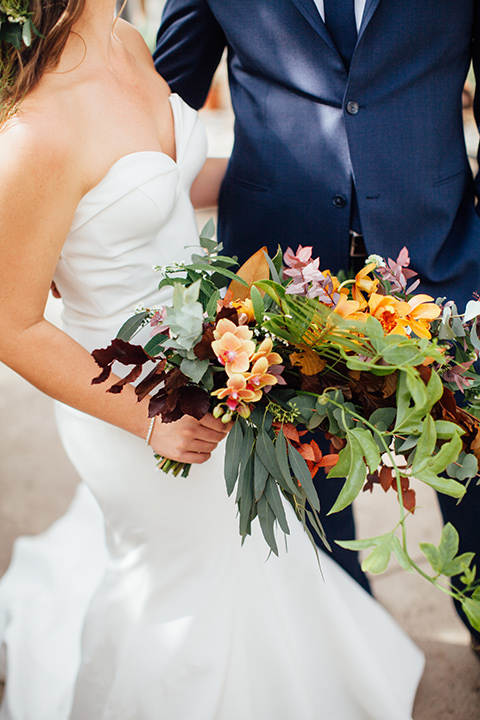 Dos-pueblos-orchid-farm-wedding-close-up-of-bride-and-groom-bride-in-a-strapless-white-gown-eith-autumn-inspired-flowers