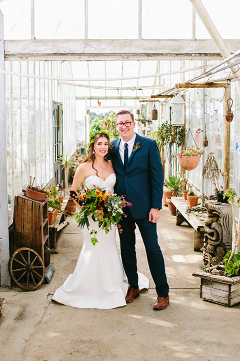 Dos-pueblos-orchid-farm-wedding-couple-smiling-at-camera-inside-glass-building-bride-in-a-fitted-gown-and-a-floral-crown
