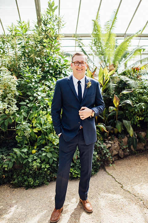 Dos-pueblos-orchid-farm-wedding-groom-smiling-in-glass-builing-wearing-a-dark-blue-suit