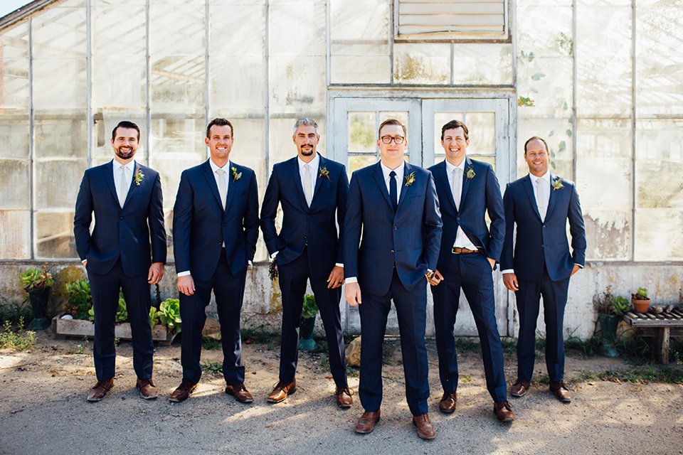 Dos-pueblos-orchid-farm-wedding-groomsmen-standing-in-a-line-wearing-dark-blue-suits