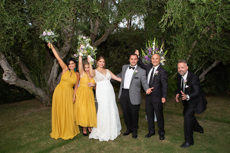 Palm-Springs-wedding-at-the-parker-bridal-party-bridesmaids-in-mustard-yellow-dresses-groomsmen-in-black-tuxedos-bride-in-a-flowing-gown-with-straps-and-a-plunging-deep-v-neckline-groom-in-a-grey-tuxedo-with-black-trim-and-black-pants