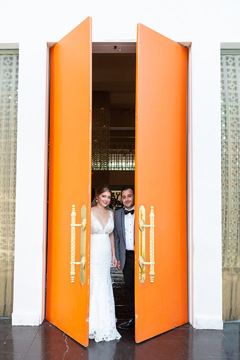Palm-Springs-wedding-at-the-parker-bride-and-groom-peeping-out-the-orange-doors-bride-in-a-flowing-gown-and-a-deep-v-neckline-groom-in-grey-tuxedo-with-black-trim