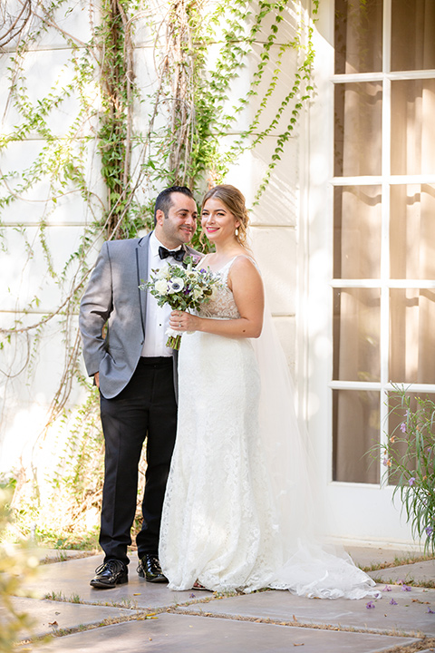 Palm-Springs-wedding-at-the-parker-bride-and-groom-smiling-bride-in-a-flowing-gown-and-a-deep-v-neckline-groom-in-a-grey-tux-with-black-trim-and-black-pants