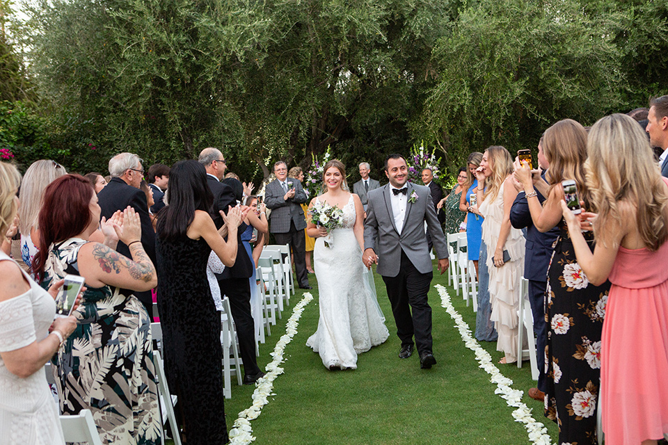 Palm-Springs-wedding-at-the-parker-bride-and-groom-walking-down-the-aisle-bride-in-a-flowing-gown-with-straps-and-a-plunging-deep-v-neckline-groom-in-a-grey-tuxedo-with-black-trim-and-black-pants