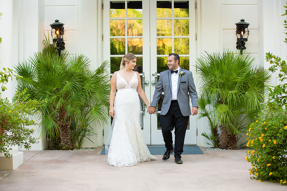 Palm-Springs-wedding-at-the-parker-bride-and-groom-walking-bride-in-a-flowing-gown-with-straps-and-a-plunging-deep-v-neckline-groom-in-a-grey-tuxedo-with-black-trim-and-black-pants