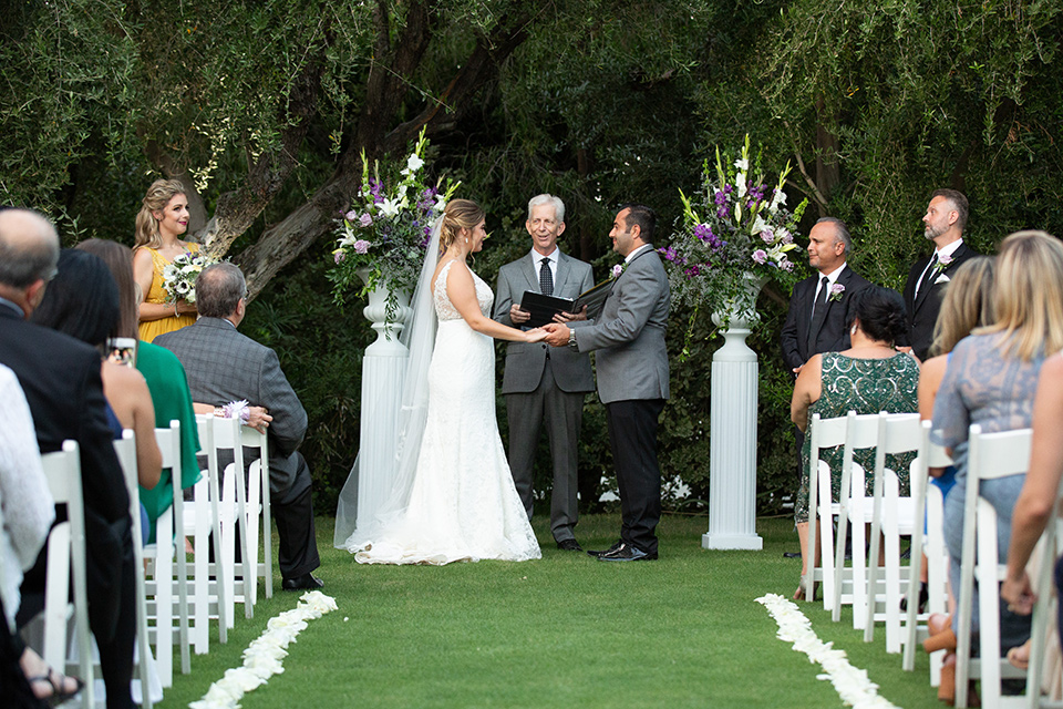 Palm-Springs-wedding-at-the-parker-ceremony-time-bride-in-a-flowing-gown-with-straps-and-a-plunging-deep-v-neckline-groom-in-a-grey-tuxedo-with-black-trim-and-black-pants