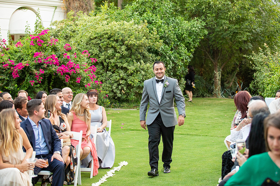 Palm-Springs-wedding-groom-walking-down-aisle-in-a-grey-tuxedo-with-black-trim-and-black-pants