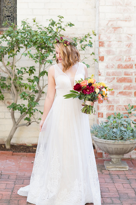 palos-verdes-shoot-bride-alone-holding-dress-bride-wearing-a-flowing-gown-with-straps-and-a-illusion-v-neck