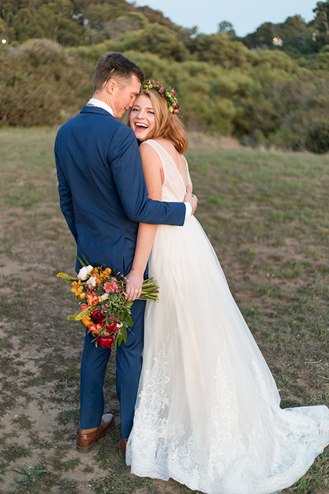palos-verdes-shoot-bride-and-groom-laughing-holding-each-other-outside-bride-wearing-a-flowing-gown-with-straps-and-a-illusion-v-neck-groom-wearing-a-colbalt-blue-suit-with-a-grey-floral-long-tie