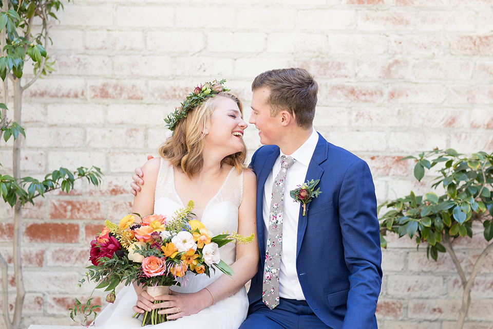 palos-verdes-shoot-bride-and-groom-sitting-and-laughing-bride-wearing-a-flowing-gown-with-straps-and-a-illusion-v-neck-groom-wearing-a-colbalt-blue-suit-with-a-grey-floral-long-tie