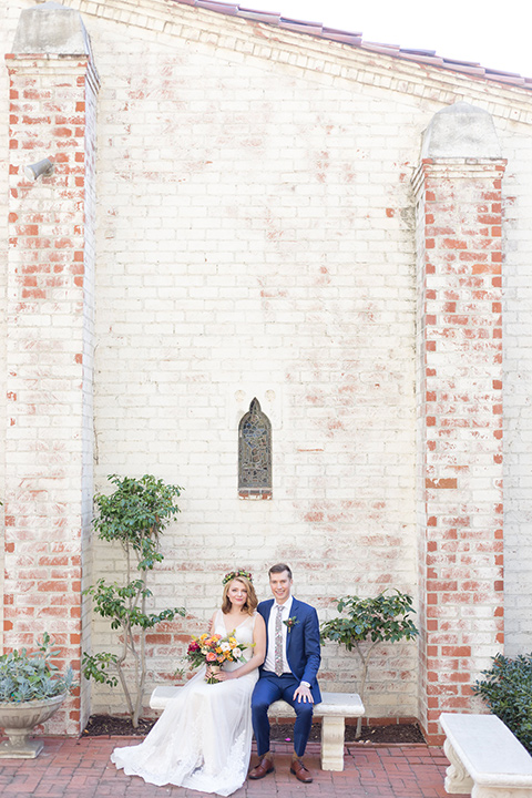 palos-verdes-shoot-bride-and-groom-sitting-with-bricks-behind-them-bride-wearing-a-flowing-gown-with-straps-and-a-illusion-v-neck-groom-wearing-a-colbalt-blue-suit-with-a-grey-floral-long-tie