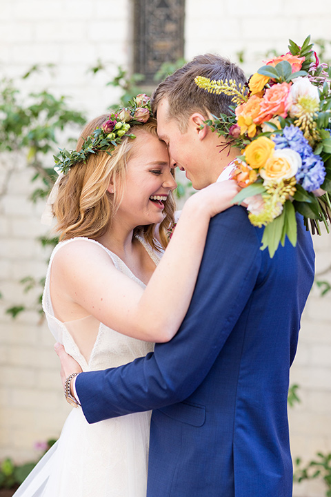 palos-verdes-shoot-bride-and-groom-toucing-heads-close-bride-wearing-a-flowing-gown-with-straps-and-a-illusion-v-neck-groom-wearing-a-colbalt-blue-suit-with-a-grey-floral-long-tie
