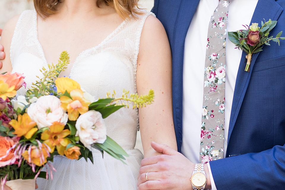 palos-verdes-shoot-close-up-on-couple-bride-wearing-a-flowing-gown-with-straps-and-a-illusion-v-neck-groom-wearing-a-colbalt-blue-suit-with-a-grey-floral-long-tie