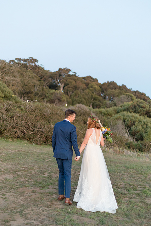 palos-verdes-shoot-couple-on-grass-bride-wearing-a-flowing-gown-with-straps-and-a-illusion-v-neck-groom-wearing-a-colbalt-blue-suit-with-a-grey-floral-long-tie