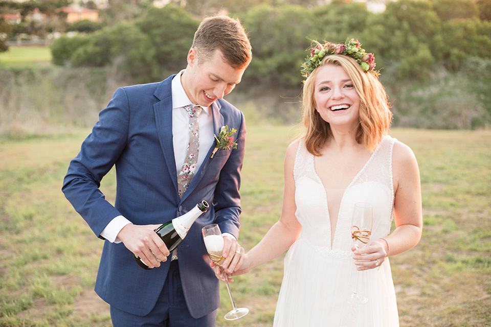 palos-verdes-shoot-pouring-chamagne-bride-wearing-a-flowing-gown-with-straps-and-a-illusion-v-neck-groom-wearing-a-colbalt-blue-suit-with-a-grey-floral-long-tie