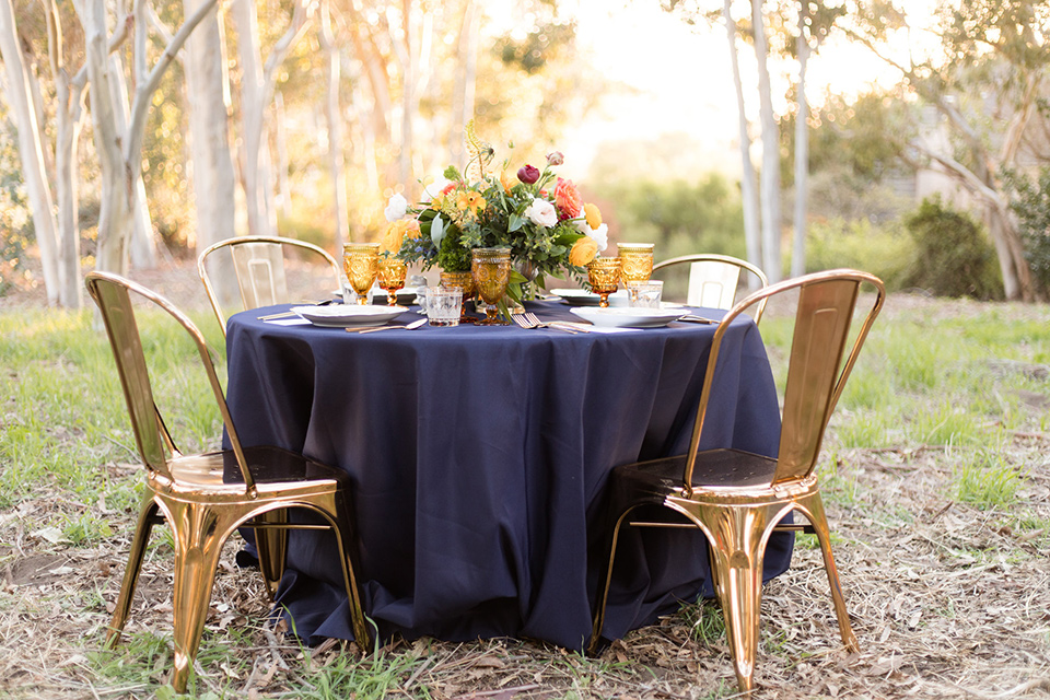 palos-verdes-shoot-tablescape-bride-wearing-a-flowing-gown-with-straps-and-a-illusion-v-neck-groom-wearing-a-colbalt-blue-suit-with-a-grey-floral-long-tie