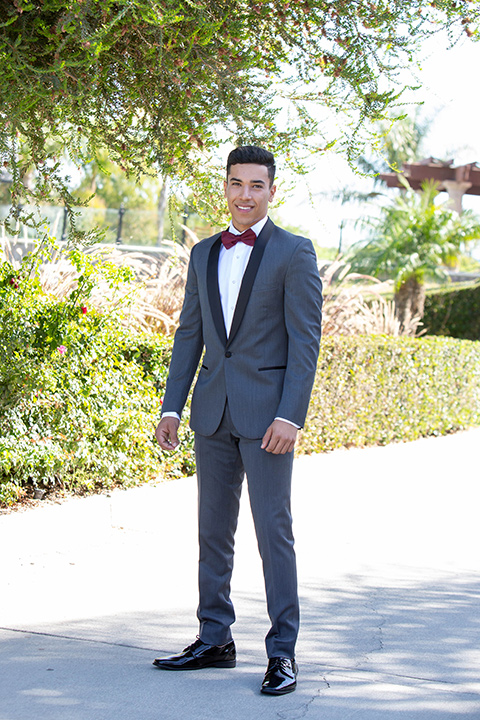 quince-shoot-chambelan-in-royal-themed-tuxedo-in-charcoal-with-a-black-trimmed-lapel-and-burgundy-bow-tie