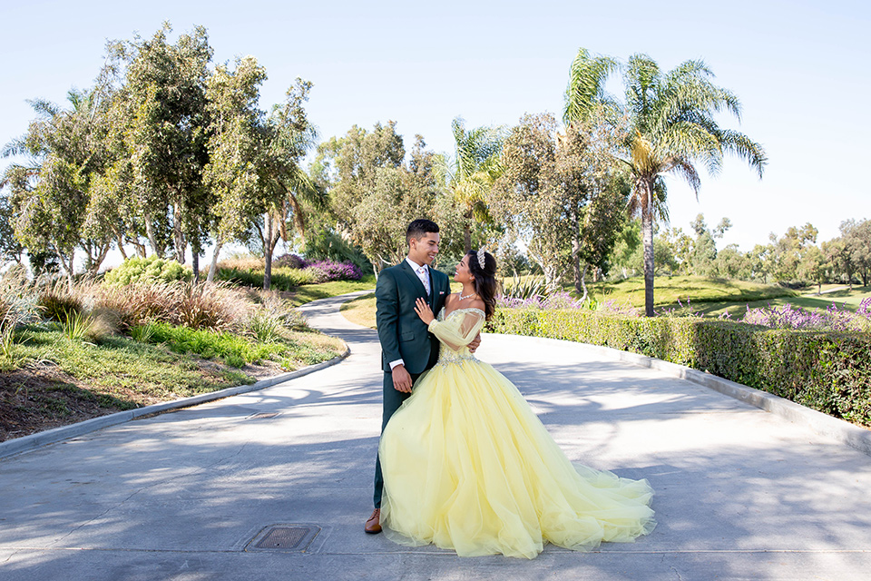 quince-shoot-enchanted-garden-theme-birthday-girl-in-a-yellow-ballgown-and-the-chambelan-in-a-dark-green-suit